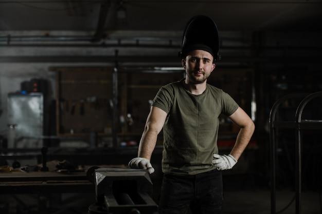 Portret młodego przystojnego męskiego spawacza w ochronnej masce na głowie