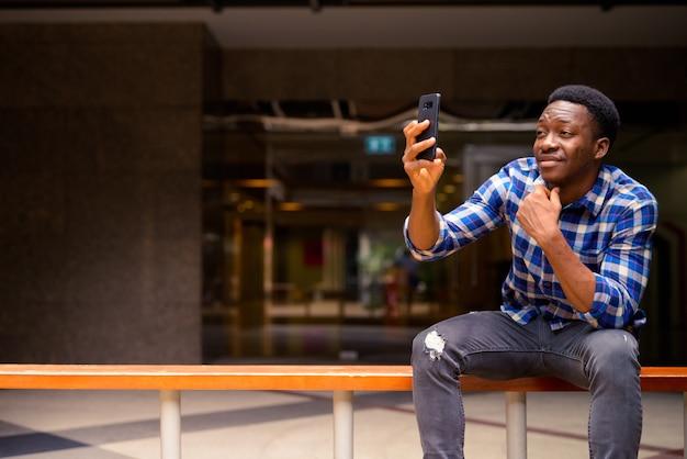 Portret młodego przystojnego mężczyzny afrykańskiego na ulicach miasta na zewnątrz