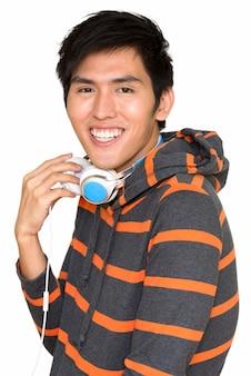 Portret młodego przystojnego mężczyzny azji uśmiecha się ze słuchawkami odizolowane na białej ścianie