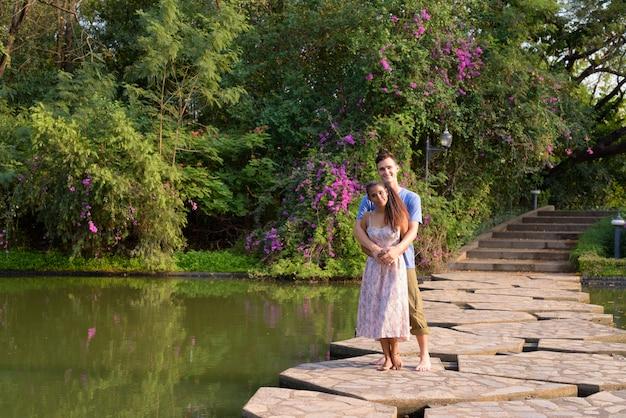 Portret młodego przystojnego mężczyzny i młodej pięknej azjatyckiej kobiety razem relaks w parku