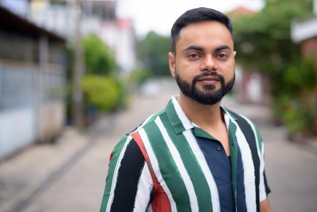 Portret młodego przystojnego mężczyzny indyjski brodaty na ulicach na zewnątrz