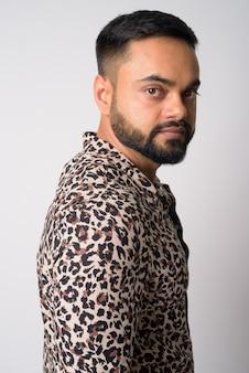 Portret młodego przystojnego mężczyzny indyjski brodaty przeciw białej ścianie