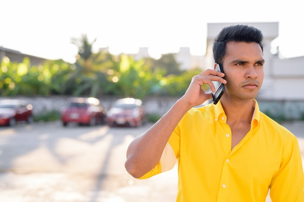 Portret młodego przystojnego mężczyzny indyjskiego na ulicach na zewnątrz