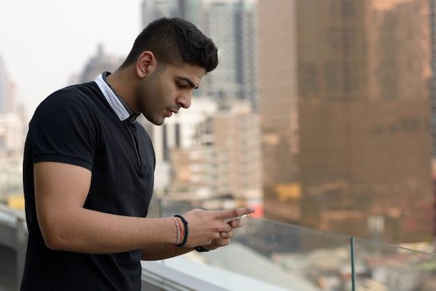 Portret młodego przystojnego mężczyzny indyjskiego z widokiem na miasto
