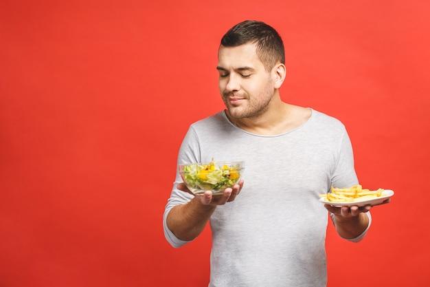 Portret młodego przystojnego mężczyzny, który pragnie fast foodów zamiast zdrowej żywności