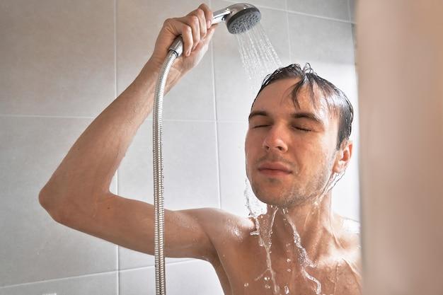 Portret młodego przystojnego mężczyzny myje się żelem pod prysznic, myje głowę szamponem w łazience w domu z bliska