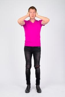 Portret młodego przystojnego mężczyzny na sobie fioletową koszulę na białej ścianie