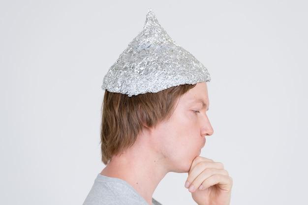 Portret młodego przystojnego mężczyzny na sobie kapelusz z folii aluminiowej jako koncepcja teorii spiskowej na białym tle