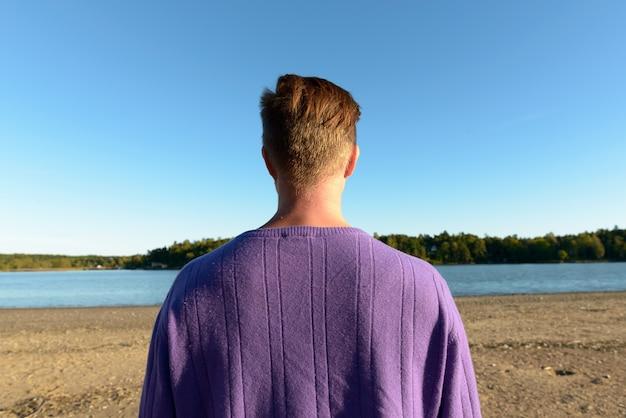 Portret młodego przystojnego mężczyzny skandynawskiego na tle pięknej scenerii brzegu