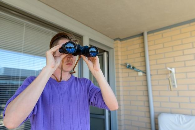 Portret młodego przystojnego mężczyzny skandynawskiego w domu na zewnątrz