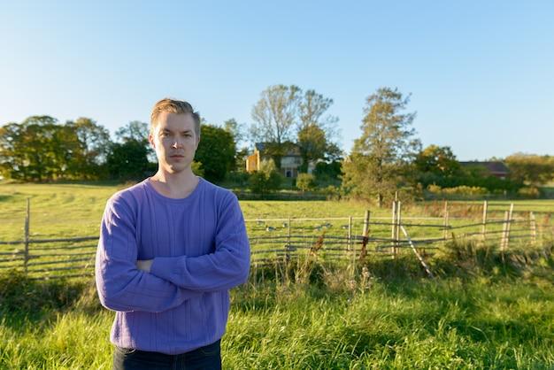 Portret młodego przystojnego mężczyzny skandynawskiego w parku w przyrodzie na zewnątrz