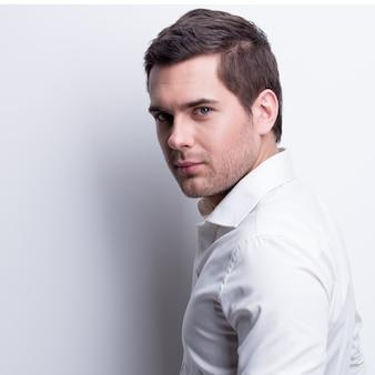 Portret młodego przystojnego mężczyzny w białej koszuli pozuje na ścianie z kontrastowymi cieniami.