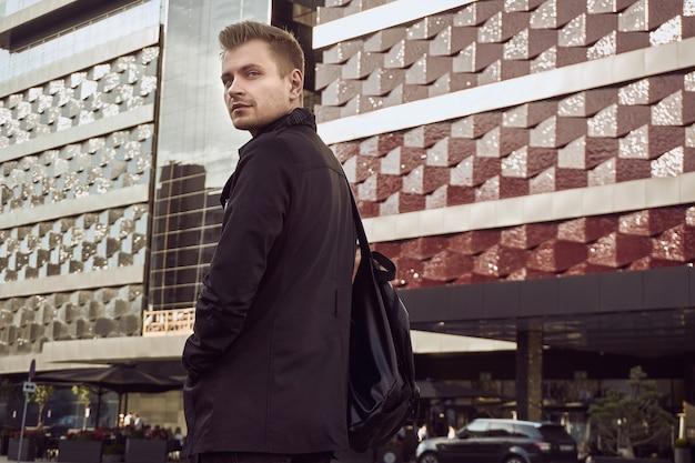 Portret młodego przystojnego mężczyzny w ciemnym płaszczu z torbą w mieście