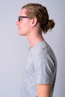 Portret młodego przystojnego mężczyzny w okularach z włosami przywiązanymi do białej ściany
