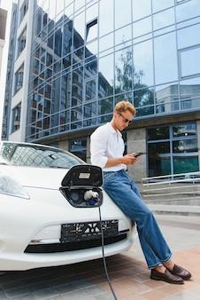 Portret młodego przystojnego mężczyzny w stroju casual, stojącego przy stacji ładującej. koncepcja ekologicznego samochodu elektrycznego