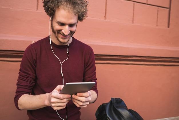Portret młodego przystojnego mężczyzny za pomocą swojego cyfrowego tabletu na zewnątrz na ulicy. technologia i koncepcja urbanistyczna.