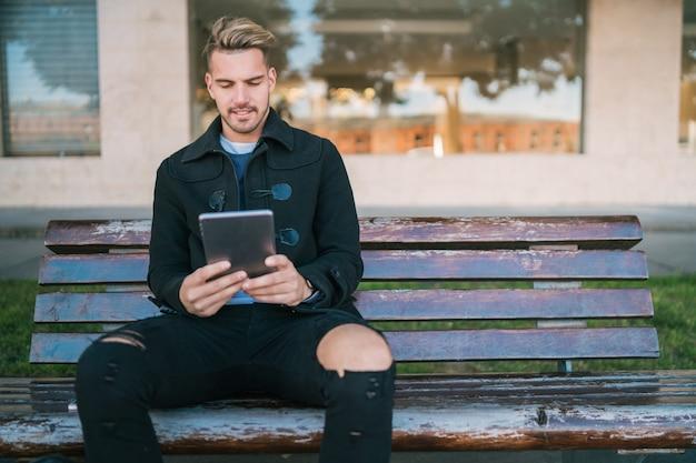Portret młodego przystojnego mężczyzny za pomocą swojego cyfrowego tabletu na zewnątrz, siedząc na ławce
