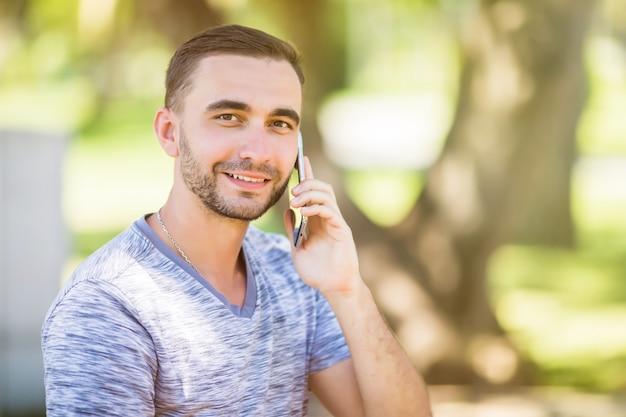 Portret młodego przystojnego młodzieńca rozmawiającego przez telefon komórkowy