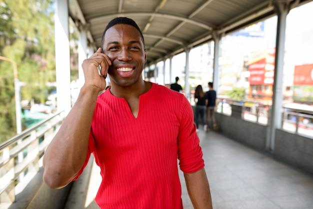 Portret młodego przystojnego muskularnego mężczyzny afrykańskiego przy kładce dla pieszych w mieście