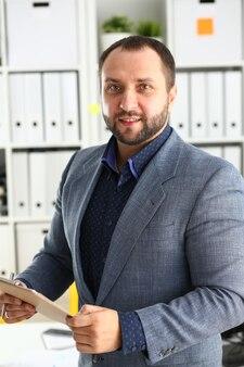 Portret młodego przystojnego obiecującego biznesmena w biurze