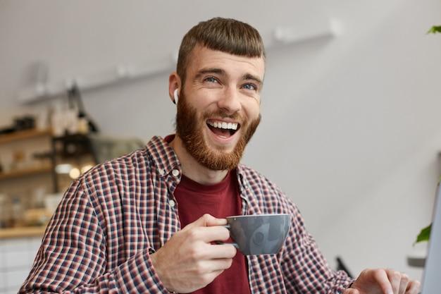 Portret młodego przystojnego, rudobrodego faceta szeroko uśmiechniętego i śmiejącego się z zabawnego żartu, cieszącego się pyszną parzoną kawą, ubranego w podstawowe ciuchy.