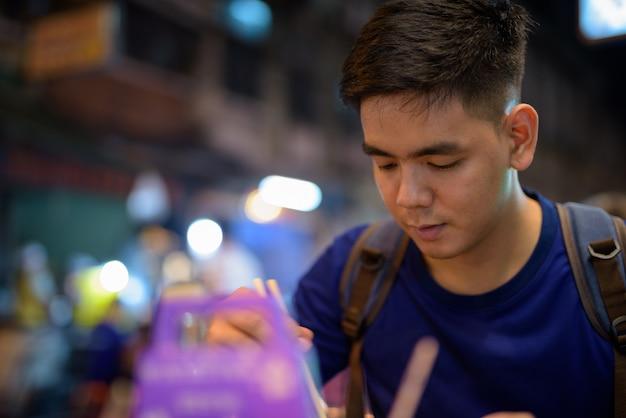 Portret młodego przystojnego turysty azjatyckiego zwiedzania w chinatown w bangkoku w tajlandii