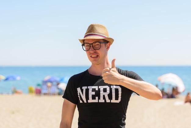Portret młodego przystojnego turysty jako frajera na plaży w hiszpanii