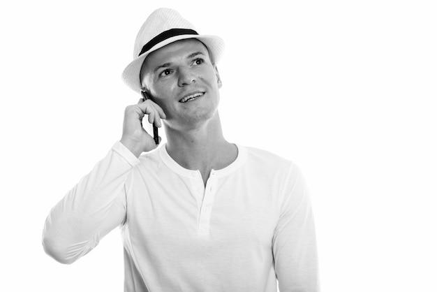Portret młodego przystojnego turysty w kapeluszu na białym w czerni i bieli