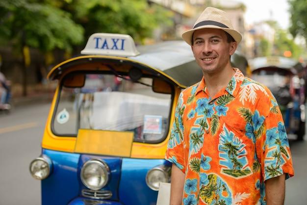 Portret młodego przystojnego turysty z tuk tuk jako lokalnego transportu publicznego w bangkoku
