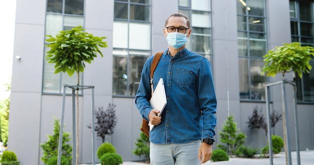 Portret młodego przystojnego ucznia płci męskiej w masce medycznej i okularach stojących na zewnątrz trzymając laptopa i patrząc na kamery. koncepcja pandemii koronawirusa. kaukaski mężczyzna na ulicy.