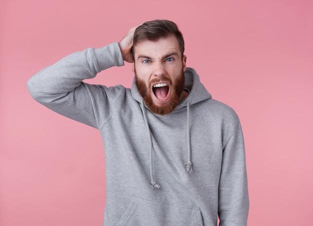 Portret młodego przystojnego, zszokowanego rudego brodacza w szarej bluzie z kapturem, wygląda złowrogo i agresywnie, stoi na różowym tle iz szeroko otwartymi ustami.