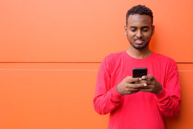 Portret młodego przystojny afrykański brodaty mężczyzna z afro włosy przed pomarańczową ścianą na zewnątrz