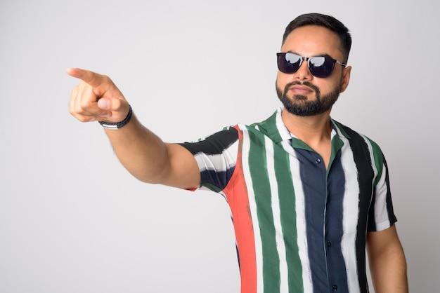 Portret młodego przystojny brodaty mężczyzna indyjski z palcem wskazującym okulary przeciwsłoneczne