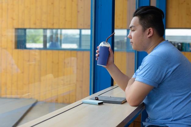 Portret młodego przystojny mężczyzna filipiński z nadwagą relaks w kawiarni