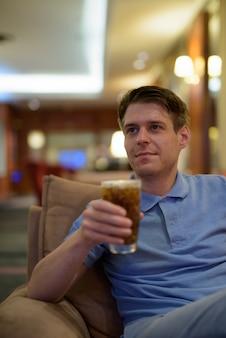 Portret młodego przystojny mężczyzna relaks w holu hotelu w mieście bangkok, tajlandia