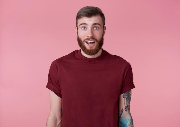 Portret młodego przystojny szczęśliwy zdumiony czerwony brodaty mężczyzna w czerwonej koszulce, stoi na różowym tle, patrzy w kamerę z szeroko otwartymi ustami i oczami.