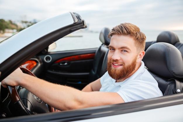 Portret młodego przystojny uśmiechnięty mężczyzna siedzi we własnym samochodzie