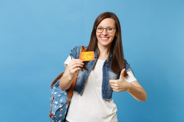 Portret młodego radosnego studenta przyjemnej kobiety w dżinsowe ubrania, okulary z plecakiem pokazując kciuk do góry trzymając kartę kredytową na białym tle na niebieskim tle. edukacja w liceum ogólnokształcącym.