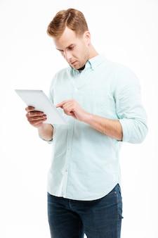 Portret młodego rudego mężczyzny korzystającego z komputera typu tablet na białej ścianie