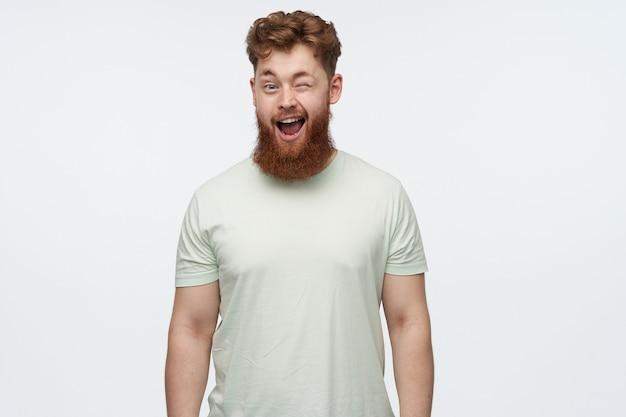 Portret młodego rudowłosego brodatego faceta nosi pustą koszulkę, czuje się szczęśliwy, uśmiecha się radośnie i mruga na biało