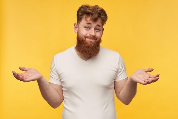 Portret młodego rudowłosego mężczyzny, nosi pustą koszulkę, unosząc ręce i zaciskając usta, z wątpliwościami