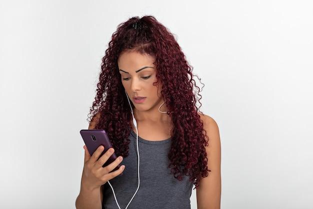 Portret młodego rudowłosego przy użyciu telefonu komórkowego ze słuchawkami, zaskoczony i patrząc na ekran. odosobniony