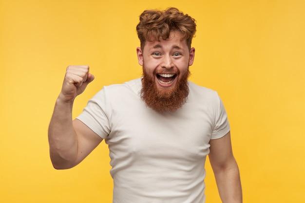 Portret młodego rudowłosego radosnego mężczyzny z gęstą brodą, szeroko się uśmiecha i ukazuje swoje mięśnie