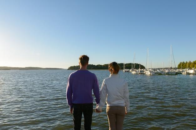 Portret młodego skandynawskiego mężczyzny i młodej azjatyckiej kobiety jako wieloetniczna para razem i zakochani na molo na świeżym powietrzu