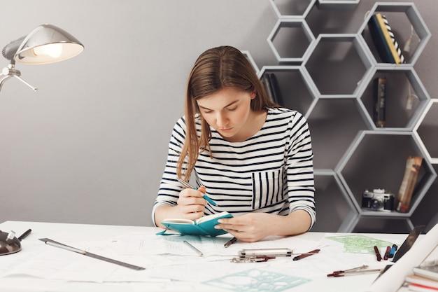 Portret młodego skoncentrowanego przystojnego żeńskiego niezależnego inżyniera o ciemnych włosach w pasiastym ubraniu, spisującego zadania na jutro. zarządzanie czasem.