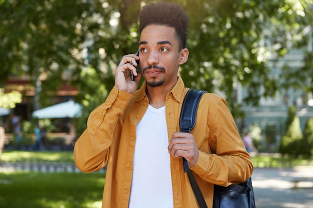Portret młodego spokojnego ciemnoskórego mężczyzny w żółtej koszuli spacerującego po parku, trzyma telefon, czekając na odpowiedź swojej dziewczyny, patrzy w zamyśleniu.