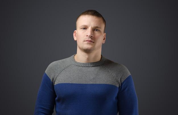 Portret młodego, spokojnego, poważnego mężczyzny. emocjonalne zdjęcie w studio na czarnej powierzchni.