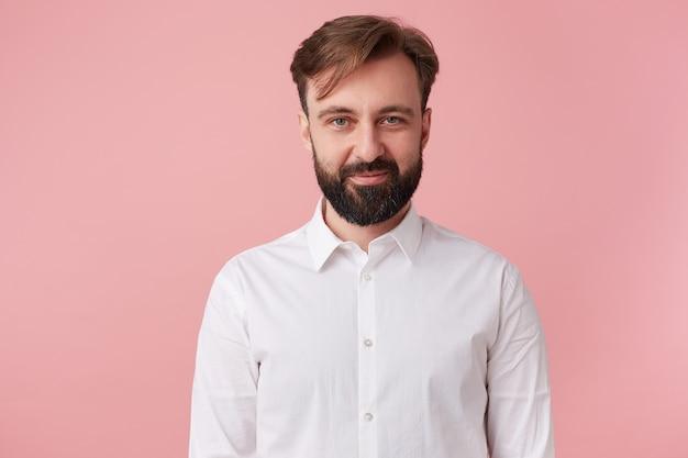 Portret młodego spokojny przystojny brodaty mężczyzna, ubrany w białą koszulę. patrząc w kamerę i nieśmiały uśmiech na białym tle nad różowym tle.