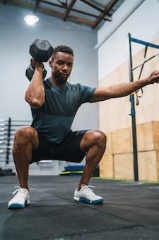 Portret młodego sportowca crossfit robi ćwiczenia z hantlami na siłowni