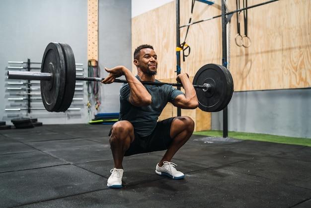 Portret młodego sportowca crossfit robi ćwiczenia ze sztangą. crossfit, sport i koncepcja zdrowego stylu życia.